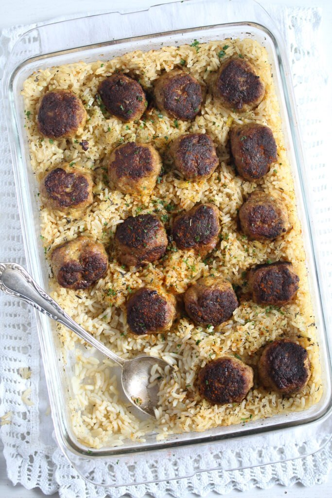 casserole dish with cooked rice and browned meatballs on top