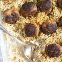 meatballs and rice being served with a spoon