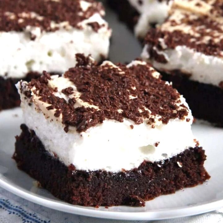 one meringue brownies topped with melting chocolate flakes, several others behind it.