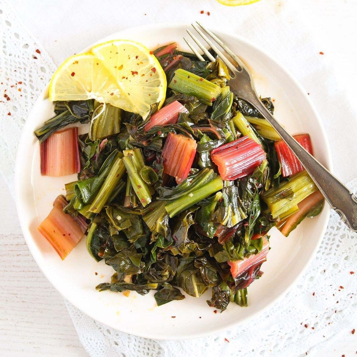 steamed swiss chard served with lemon slices on a white plate