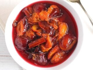 stewed plums in a small white bowl with cinnamon and star anise on top