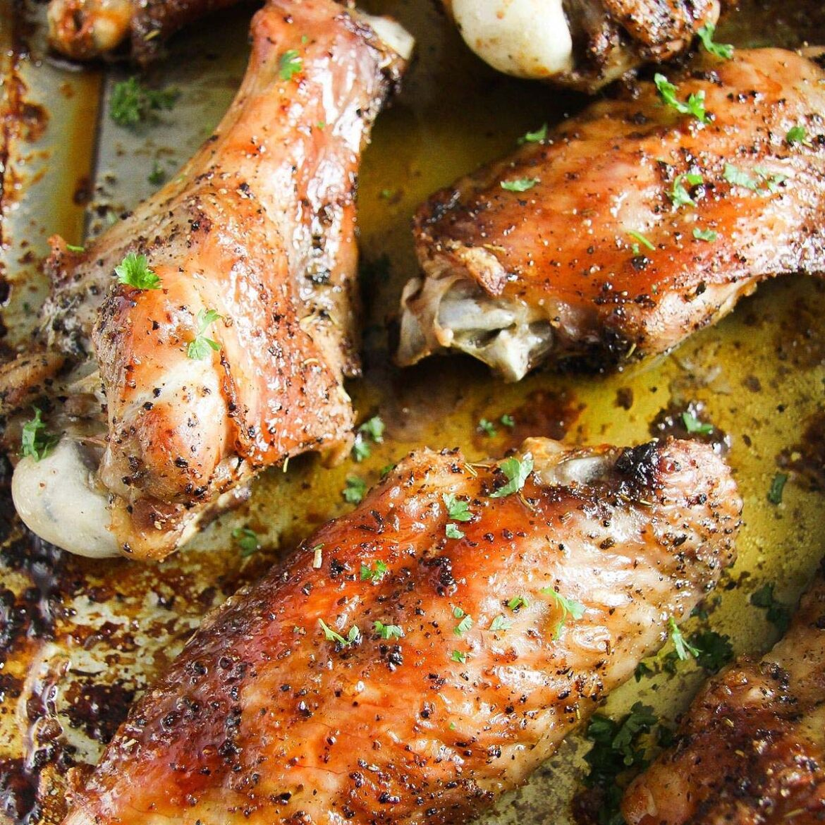 baked turkey wings in a roasting tin with parsley