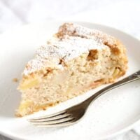 vegan apple cake sliced on a small plate with fork.