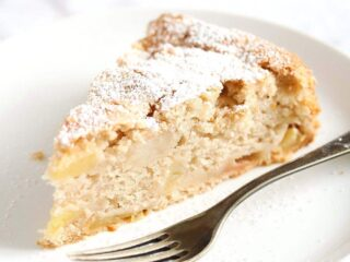 vegan apple cake sliced on a small plate with fork