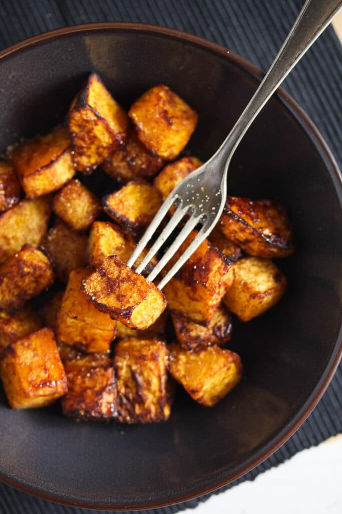 brown sugar and cinnamon butternut squash pieces in a dark bowl