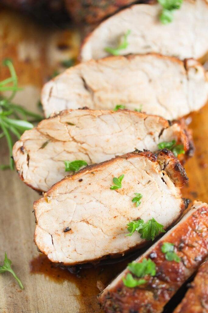white slices of air fried pork tenderloin sprinkled with parsley