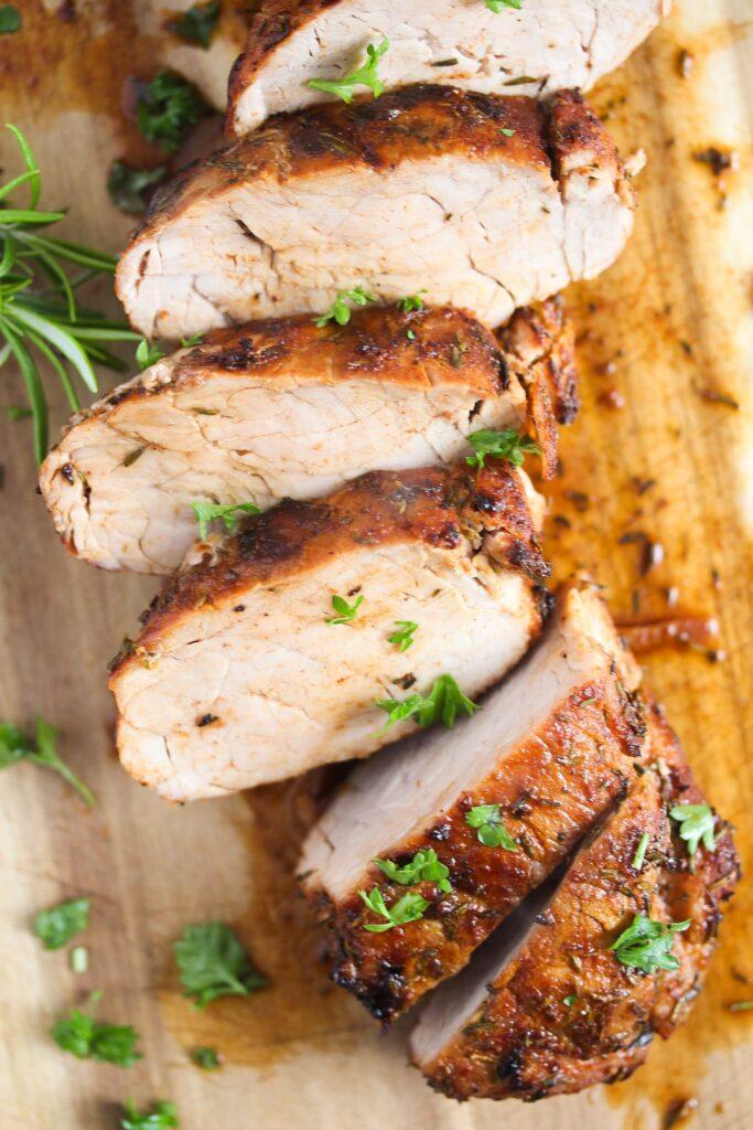 slice pork tenderloin sprinkle with fresh parsley on a wooden board