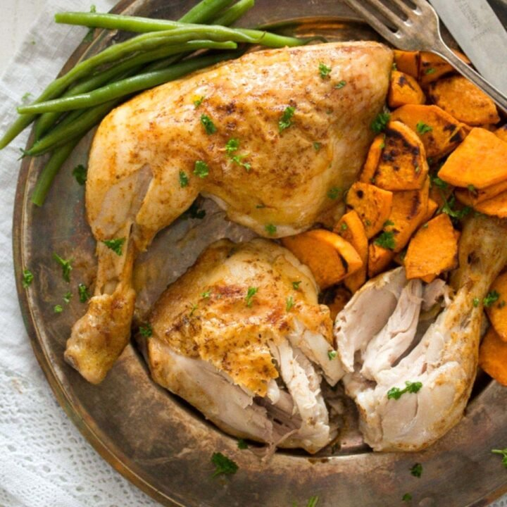 baked chicken leg quarters served with green beans and sweet potatoes on a vintage plate.