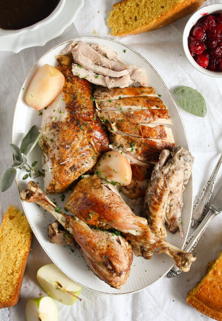 platter with carved dutch oven turkey served with cranberry sauce