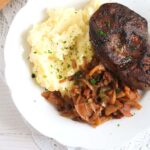 a large piece of liver served with onions, apples and mashed potatoes