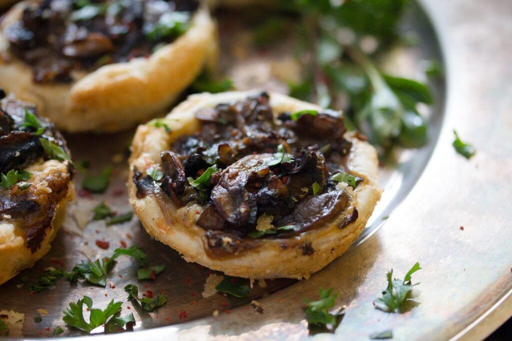 puff pastry mushroom pies with herbs on a silver platter