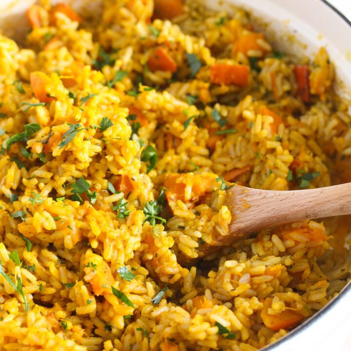 orange rice with pumpkin cubes and parsley in a white dutch oven