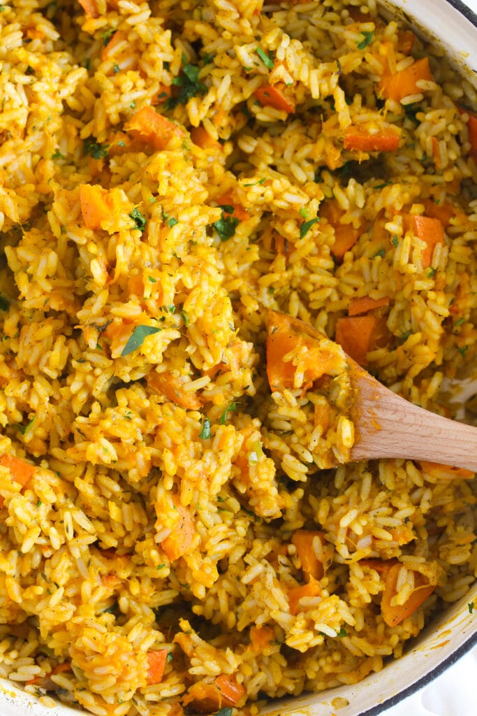 close up of pumpkin rice stirred with a wooden spoon