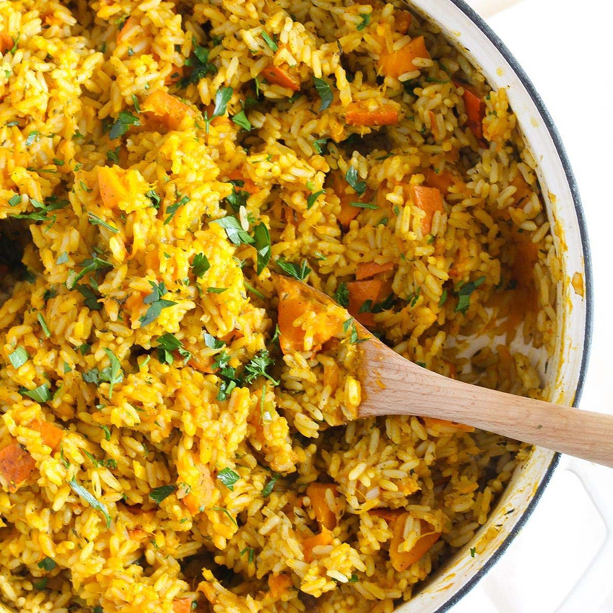 brightly colored pumpkin rice in a dutch oven seen from above
