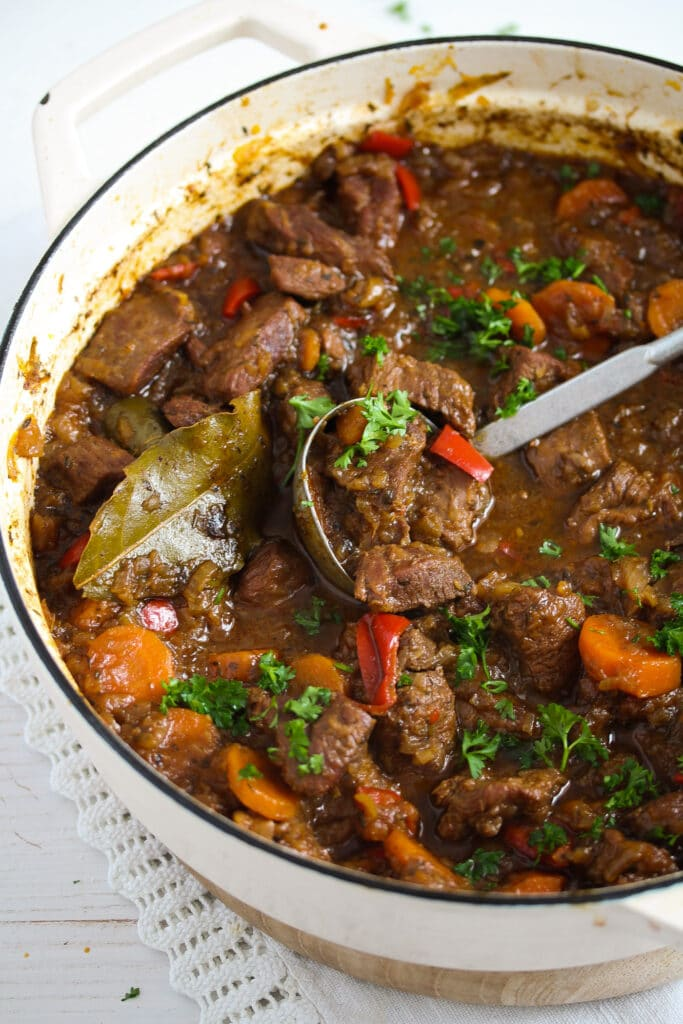 dutch oven full of stew with turkey, vegetables and gravy