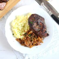 turkey liver with apple onions sauce and mashed potatoes on a large plate