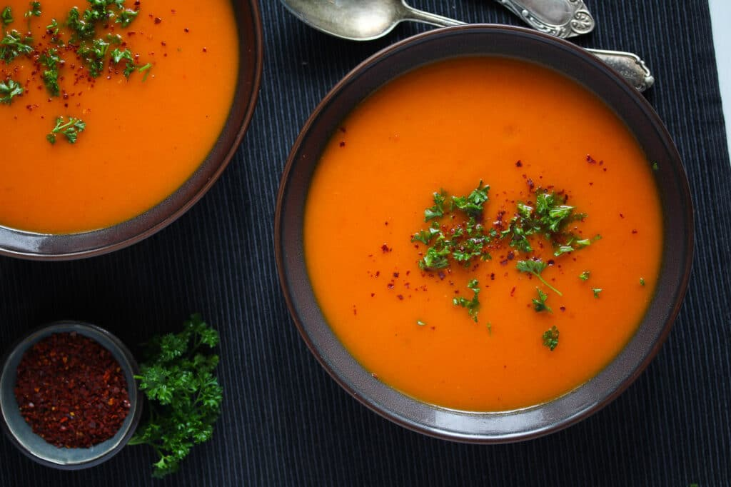 bowls with hot orange colored soup on a black table cloth