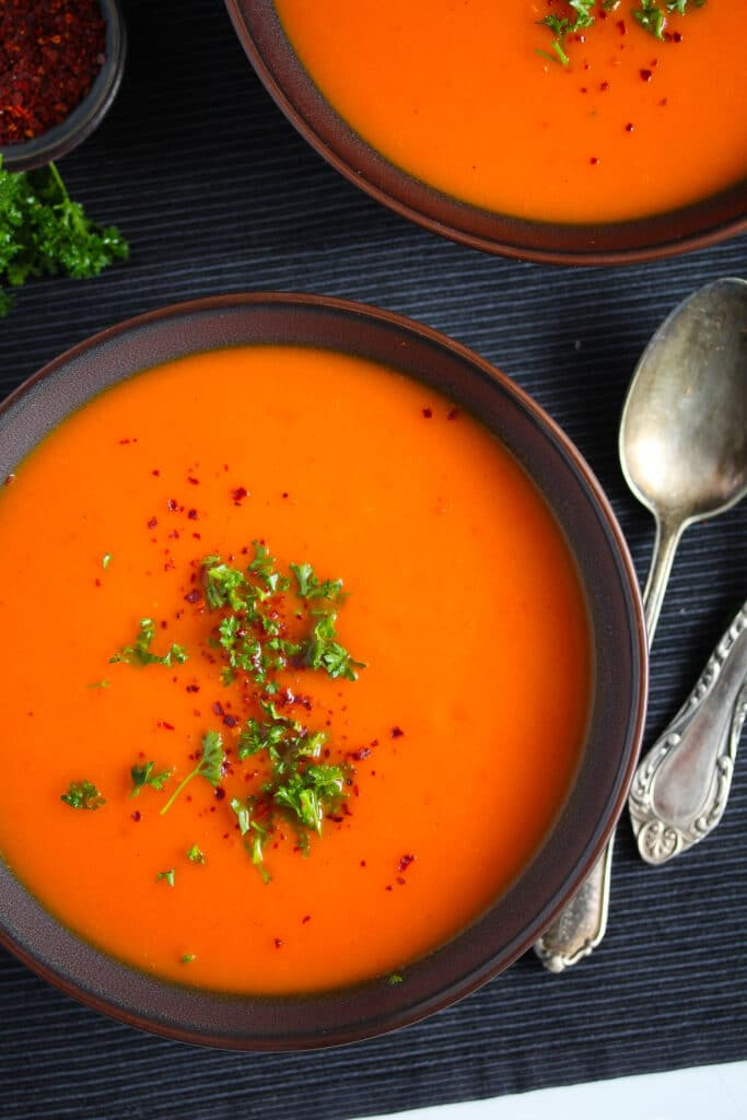 close up of red soup with bell peppers and butternut squash