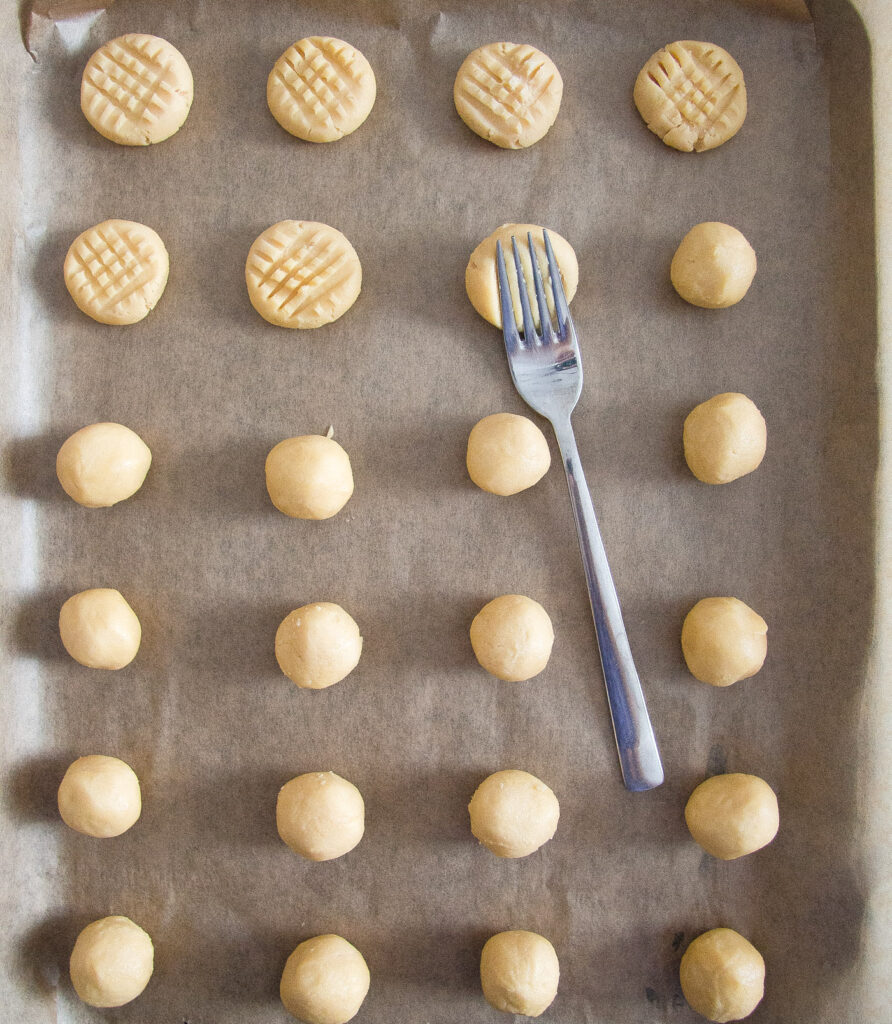 cookie dough balls being pressed with a fork on a baking tray
