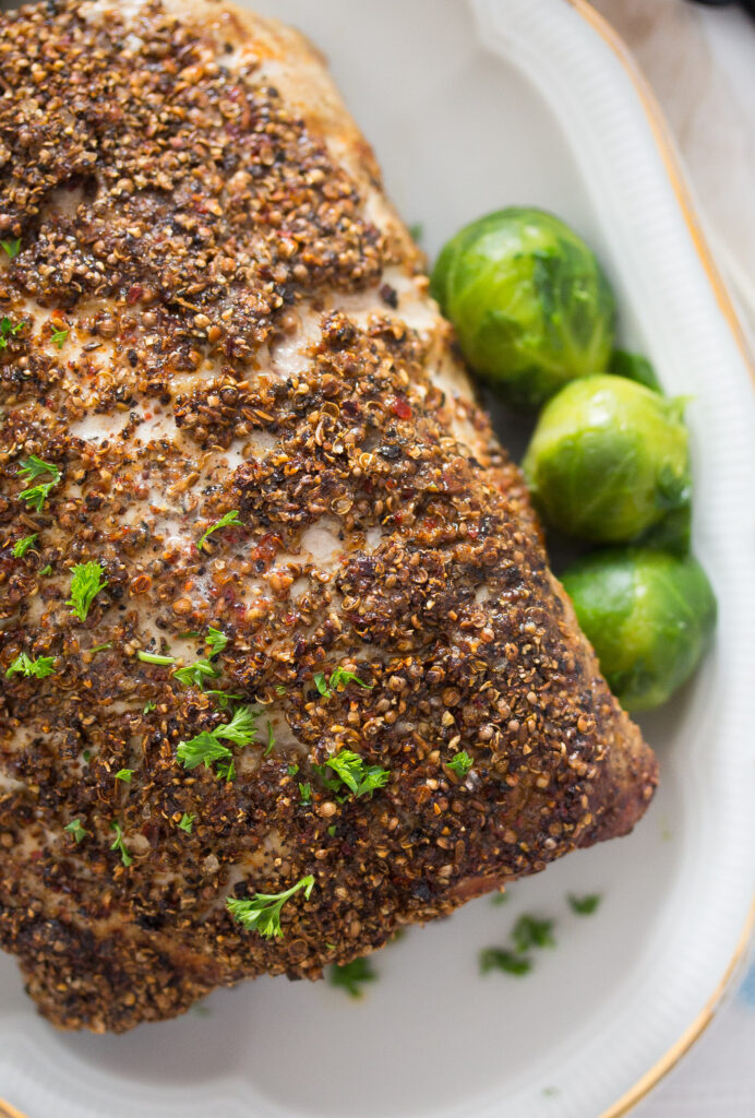 close up crusted boneless pork loin with brussels sprouts