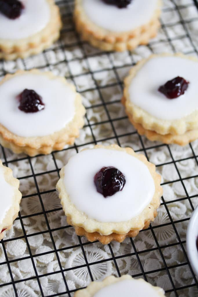 iced biscuits with raspberry jam and candied cherry on top