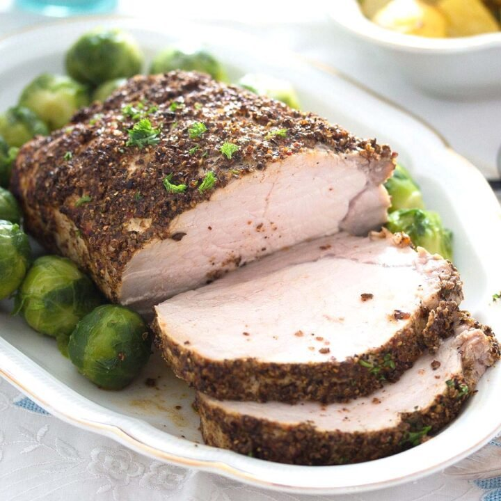 spicy pork roast sliced on a platter with brussels sprouts