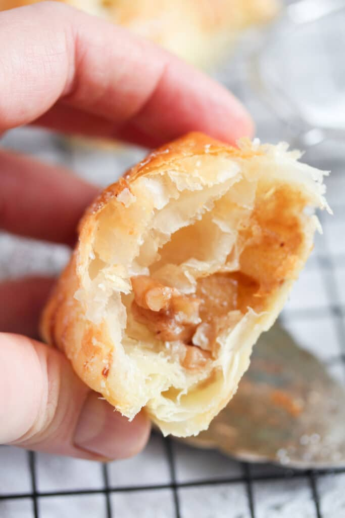 hand holding half of apple filled pastry