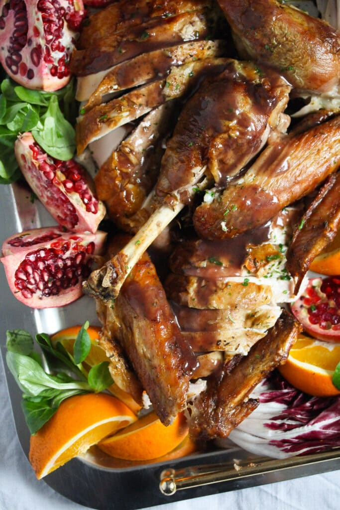 turkey legs and wings on a plate with oranges and pomegranate