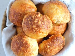 cheese buns in a basket lined with white kitchen cloth