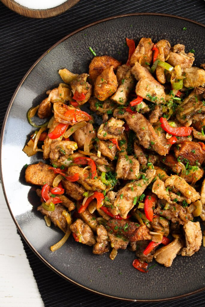 chinese salt and pepper chicken with vegetables served on a large plate