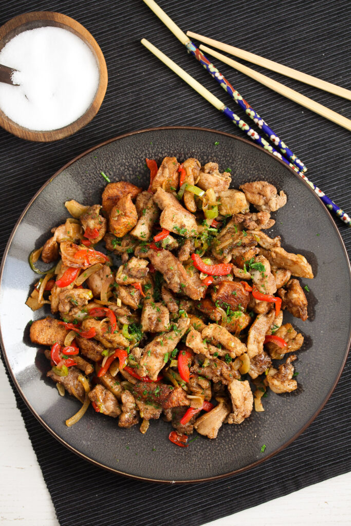chicken and colorful vegetable pieces with chopsticks
