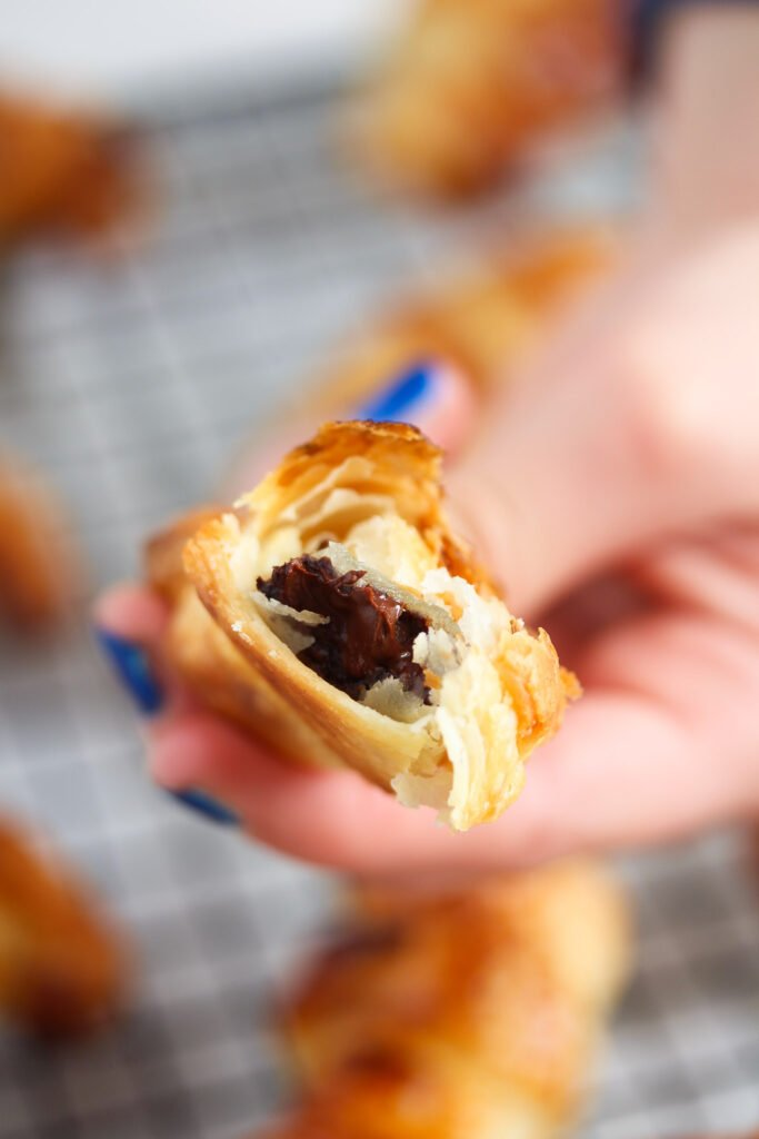 girl hand with blue fingernails holding an open pastry filled with chocolate