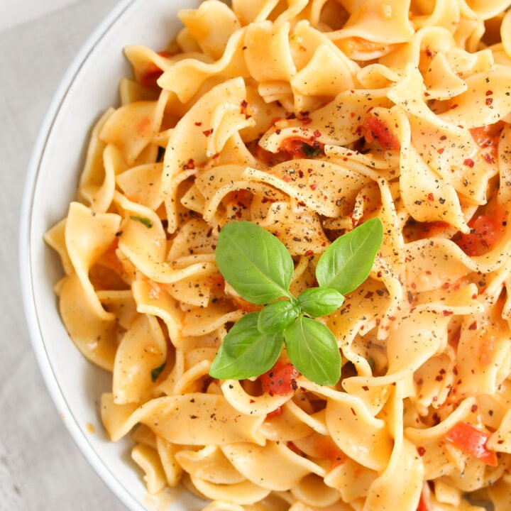 overhead shot of a bowl of pasta with tomato and coconut sauce