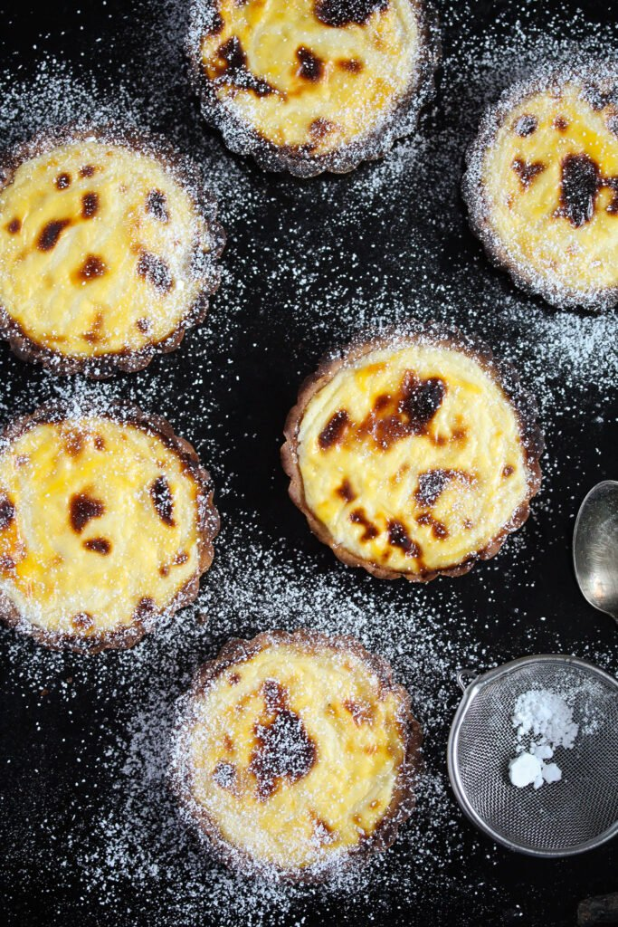 overhead shot of many hokkaido baked cheese tarts on a black board