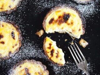 hokkaido cheese tarts on a black board and a fork