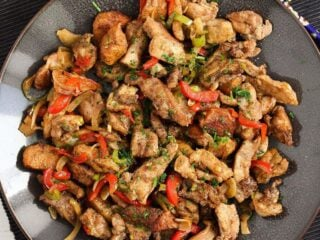 salt and pepper chicken on a brown plate overhead shot