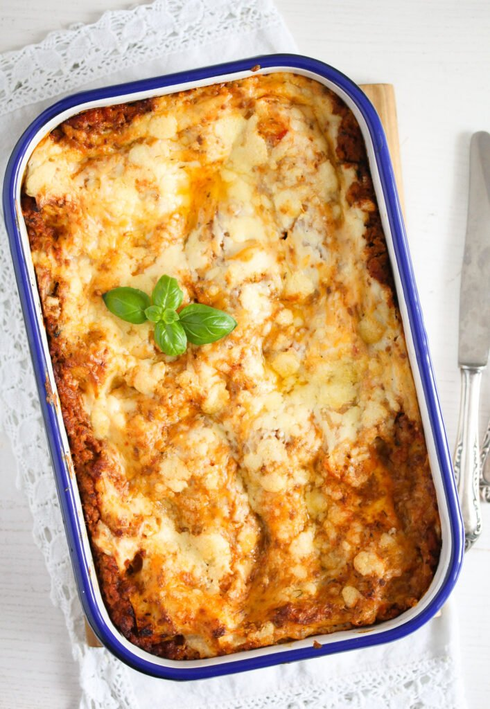 lasagna in a baking dish with meat sauce and bechamel