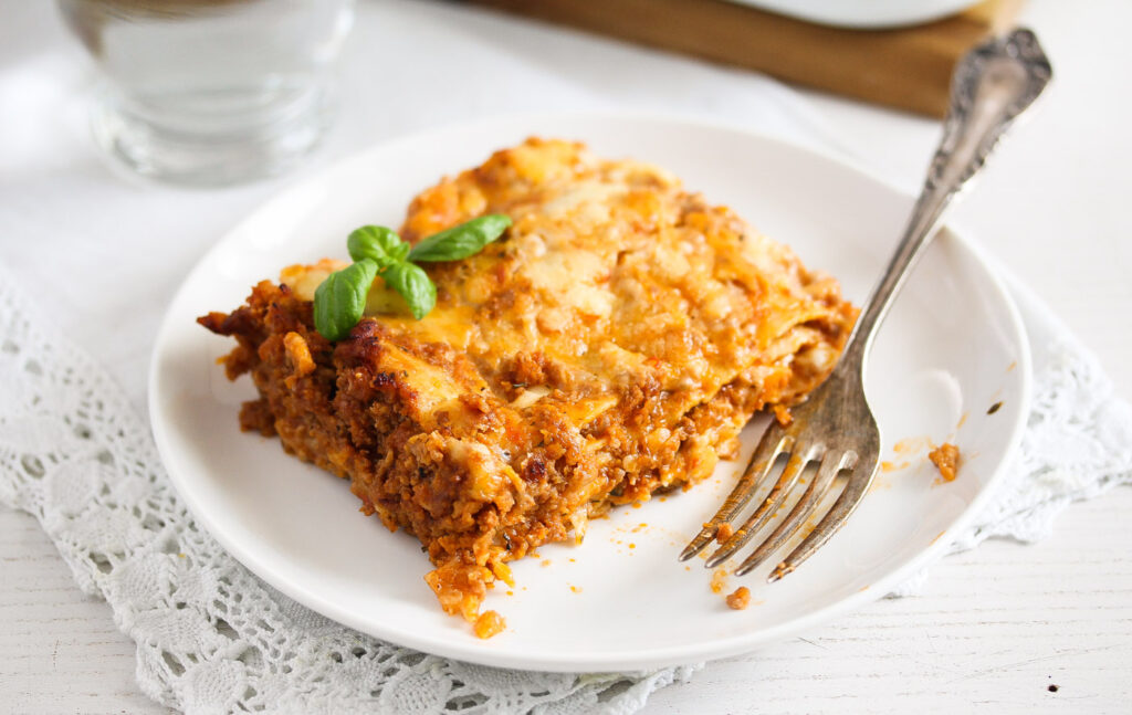 slice of pasta dish with meat sauce and bechamel on a white plate