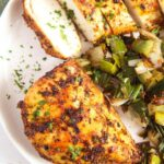 chicken breast with leeks on a plate.