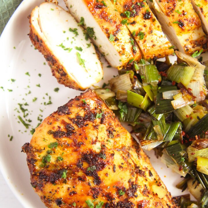 chicken breast without breading served with cooked leeks.