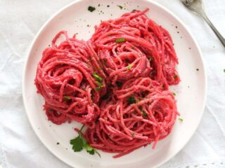 beetroot pasta on a small white plate sprinkled with parsley