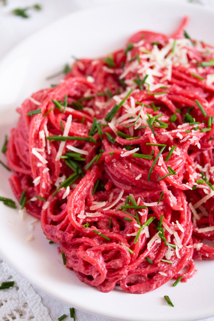 beetroot pasta dish sprinkled with parmesan close up
