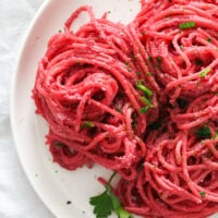 red spaghetti coated with beetroot sauce and topped with parsley