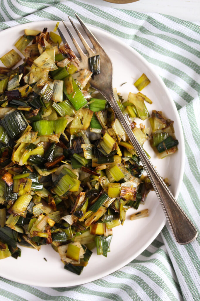 plate with sauteed leeks on a striped kitchen cloth.