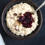 bowl of arroz con leche with blueberry sauce.