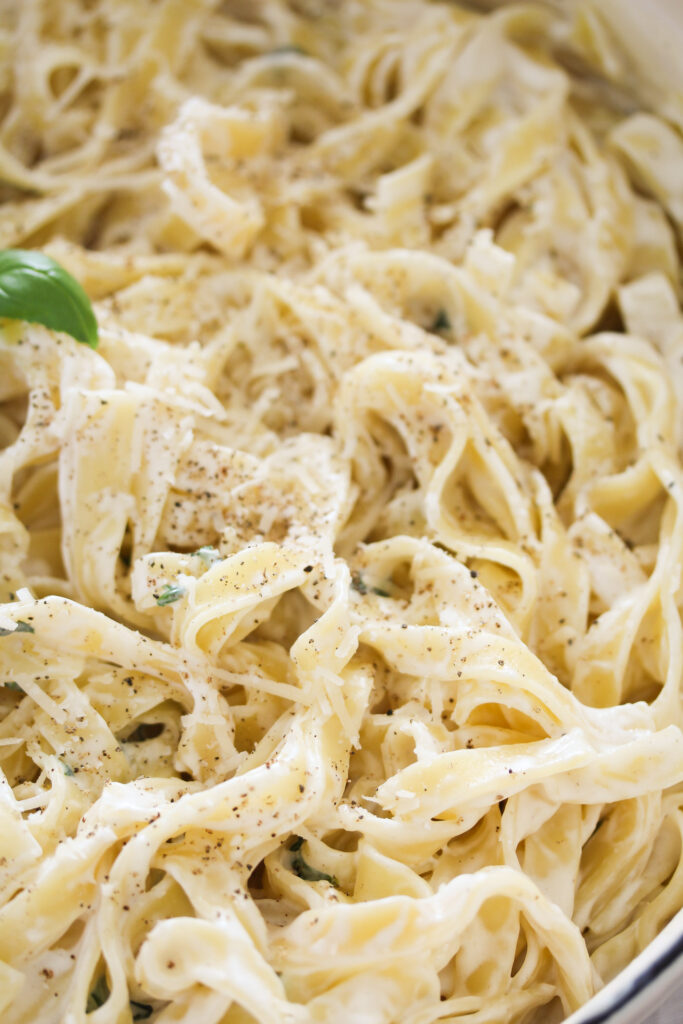 close up creamy tagliatelle with cheese and basil sauce.