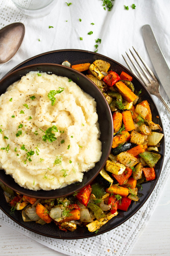 bowll of celery root mash served with roasted vegetables.