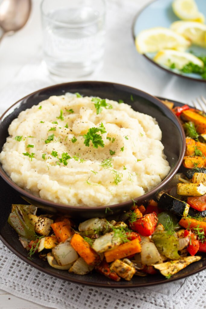 celery root puree in a small brown bowl served with veggies.