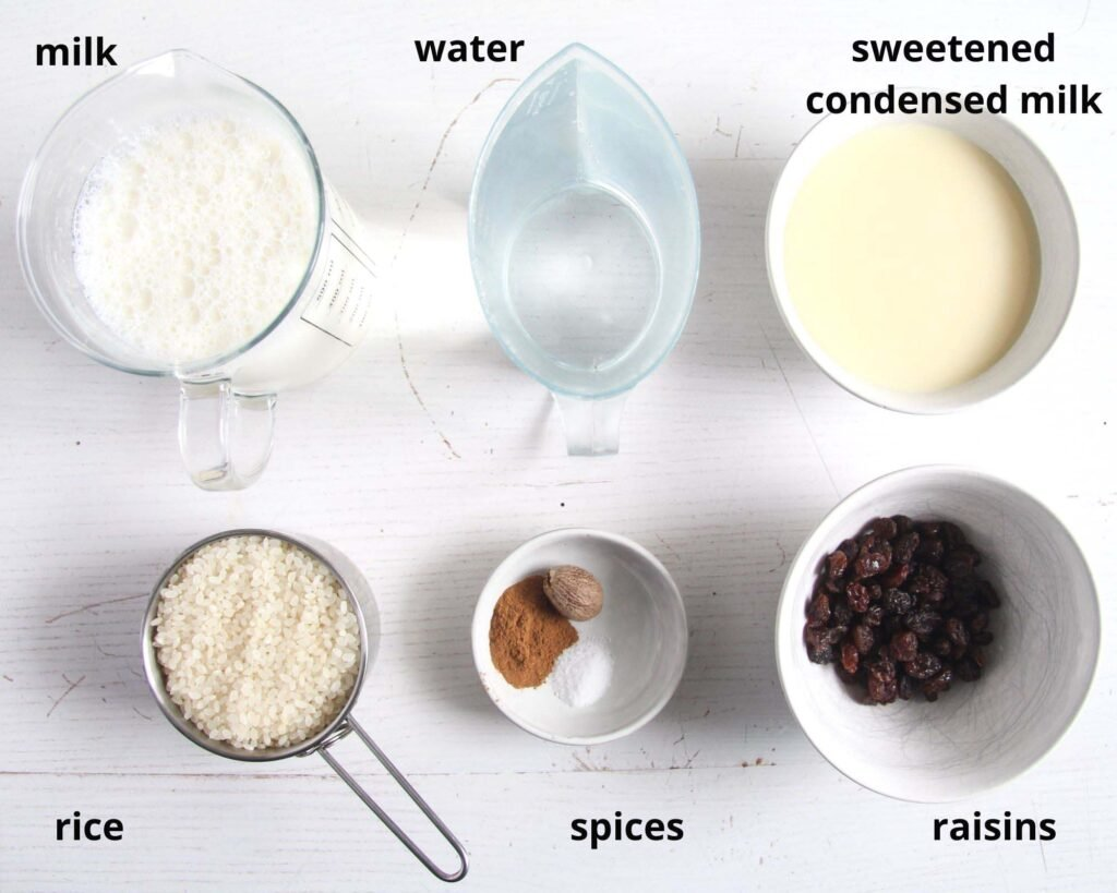 milk, water, sweetened condensed milk, rice, spices and raisins in bowls.
