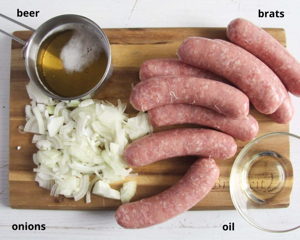 raw sausages, sliced onion, beer and oil on a wooden board